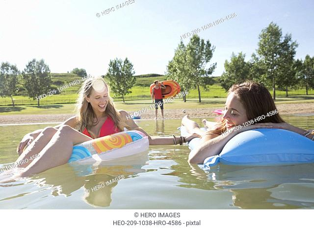 Female friends relaxing on inflatable rafts