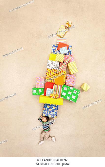 Boy balancing stack of presents