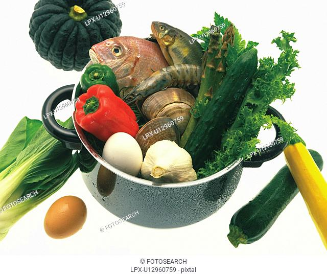 Selection of fresh vegetables, seafood and eggs in a pot