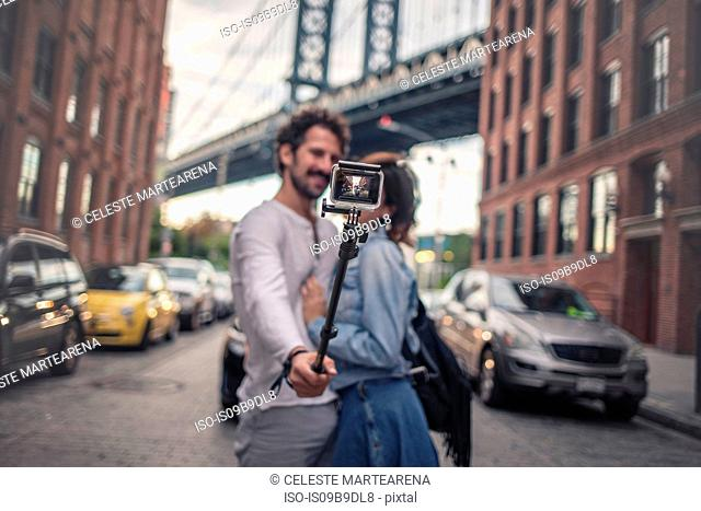 Couple taking photo with selfie stick, Brooklyn, New York, US