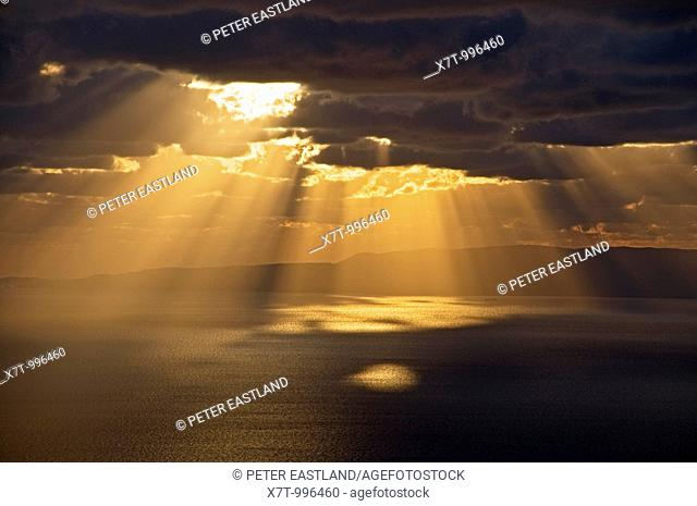 Sun bursting through clouds on the gulf of Messinia near Langada in the Outer Mani, southern Peloponnese, Greece