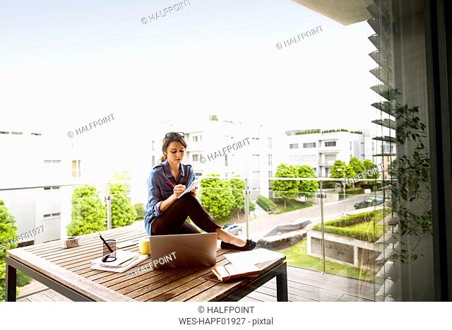 Woman working on balcony at home