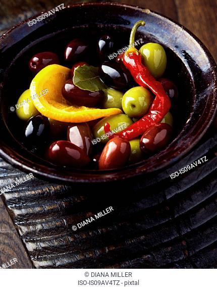 Green olives, black olives, red chilli, orange slice and bay leaf in vintage wooden bowl