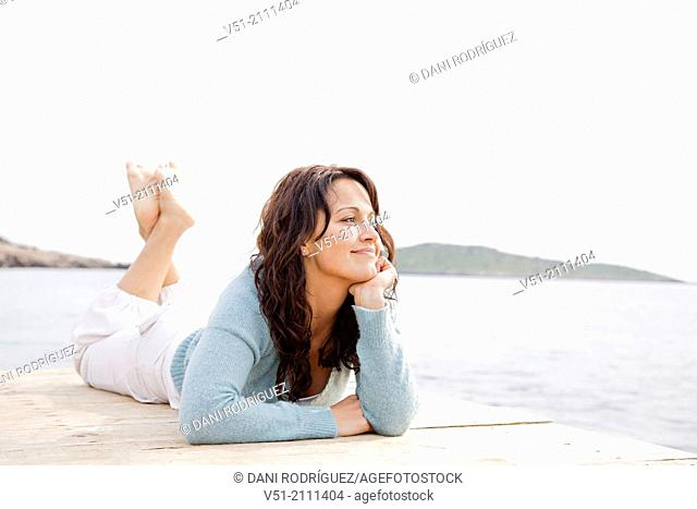 Pretty brunette woman lying on a seaside Pier