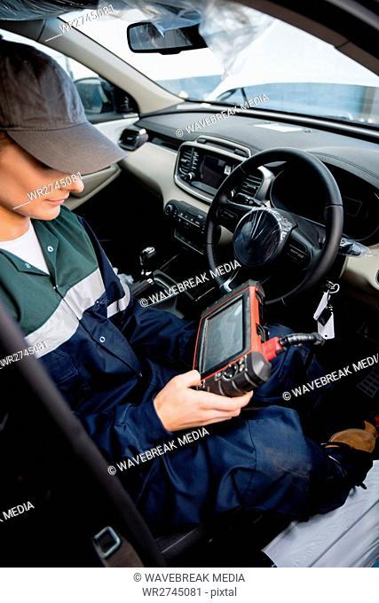 Female mechanic using electronic diagnostic device
