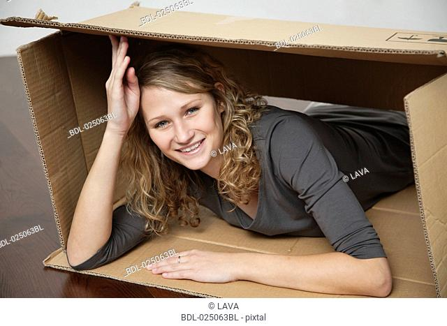 young woman lying in cardboard box