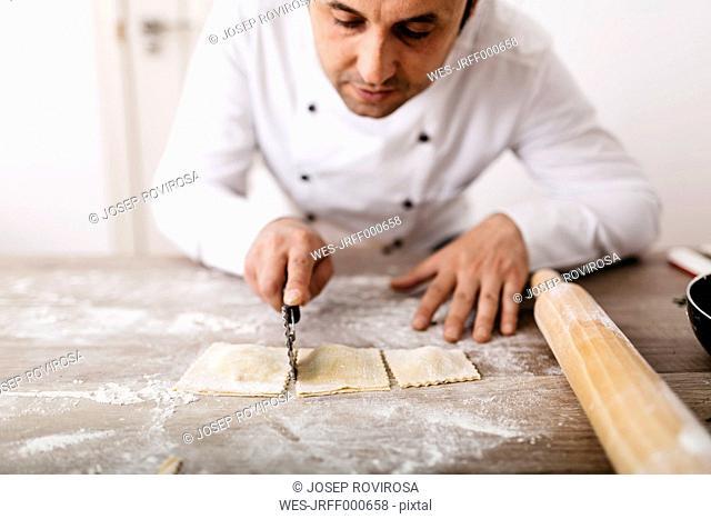 Chef cutting fresh ravioli