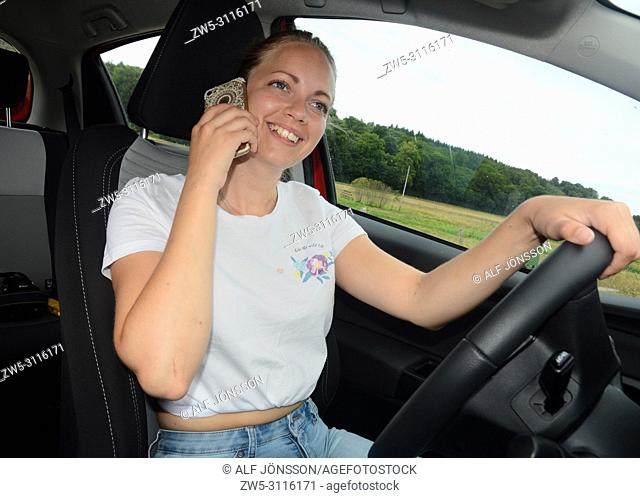 Young woman, 25 years old, talks in a mobil phone while she drive a car on a country road in Scania, Sweden, Europe