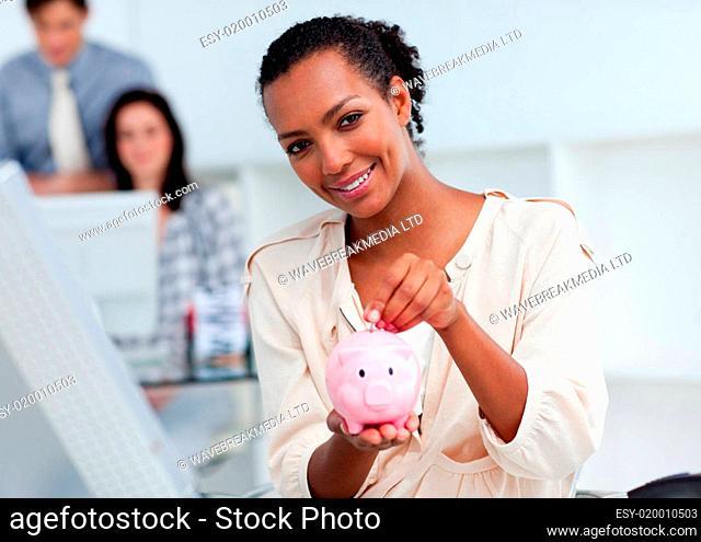 Confident businesswoman saving money in a piggy-bank