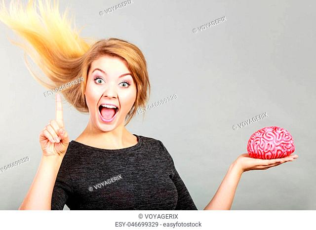Happy blonde woman holding brain pointing her finger up having something on mind, thinking of idea