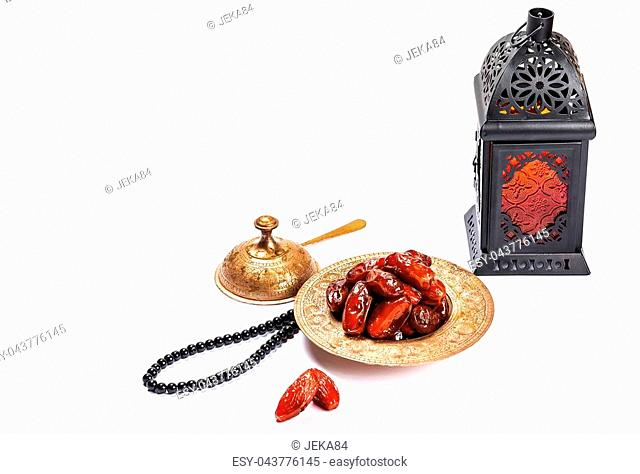 The Muslim feast of the holy month of Ramadan Kareem. Beautiful background with a shining lantern Fanus and dried dates on white