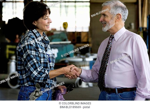 Businessman shaking hands with female warehouse worker