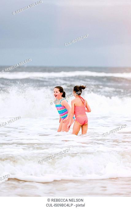 Two girls standing in ocean waves, Dauphin Island, Alabama, USA