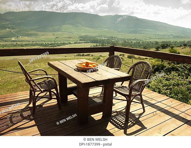 tarifa, cadiz, andalusia, spain, a table and chairs set on a terrace with a beautiful view of the landscape
