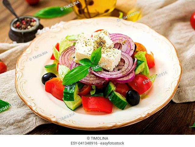 Greek salad with fresh tomato, cucumber, red onion, basil, lettuce, feta cheese, black olives and a Italian herbs on plate