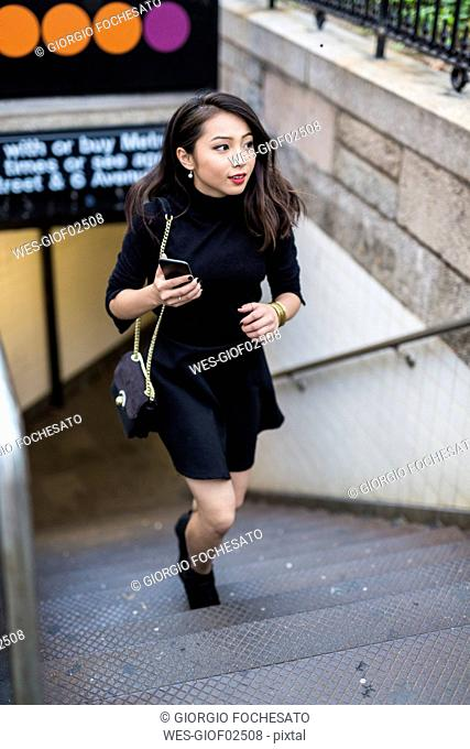 USA, New York City, Manhattan, young woman dressed in black walking upstairs