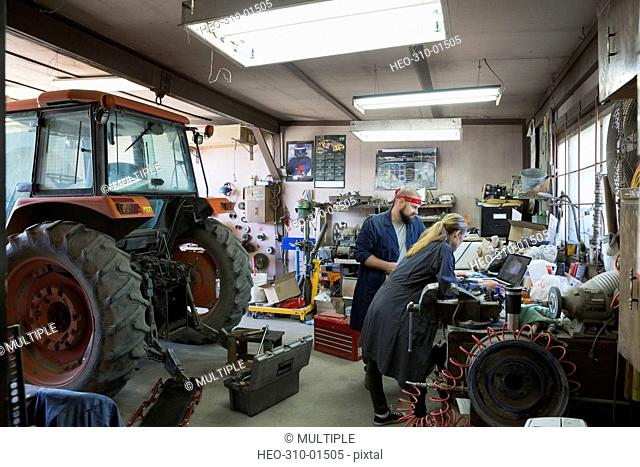 Mechanics working at laptop near tractor in workshop