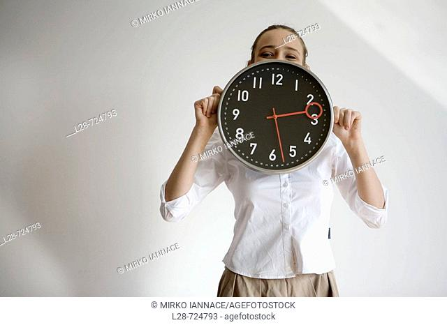 Portrait of a businesswoman hiding her face behind a clock