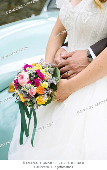 Hands of bride and groom with bouquette