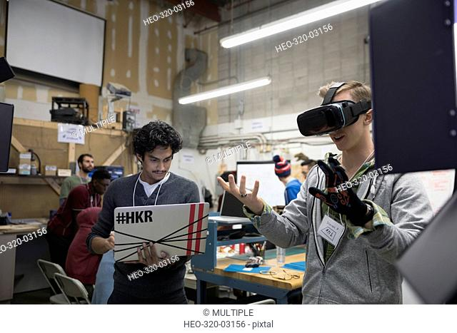 Team of male hackers with virtual reality simulator working hackathon at laptop in workshop