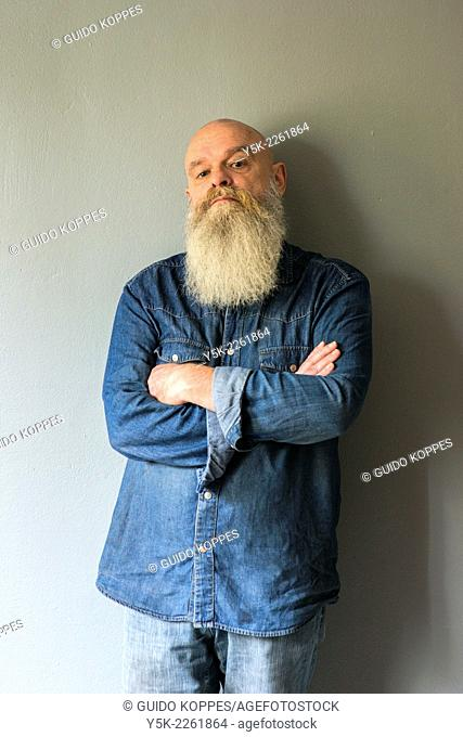 Tilburg, Netherlands. Portrait of a bald man with beard, standing against a grey wall