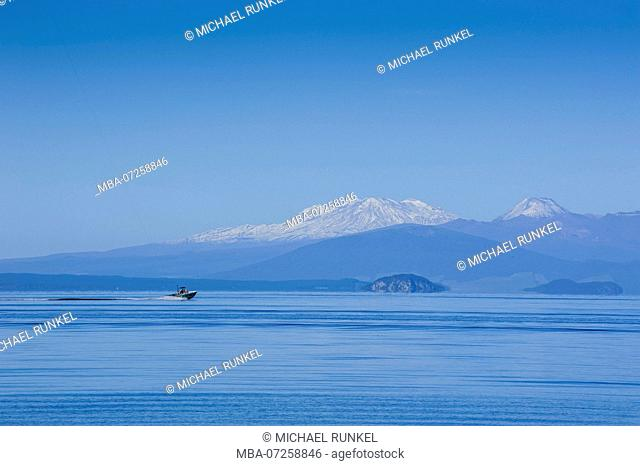 The blue waters of Taupo lake with the Tongariro National Park in the background, North Island, New Zealand