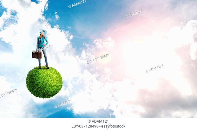 Beautiful woman traveler in hat with suitcase on green planet
