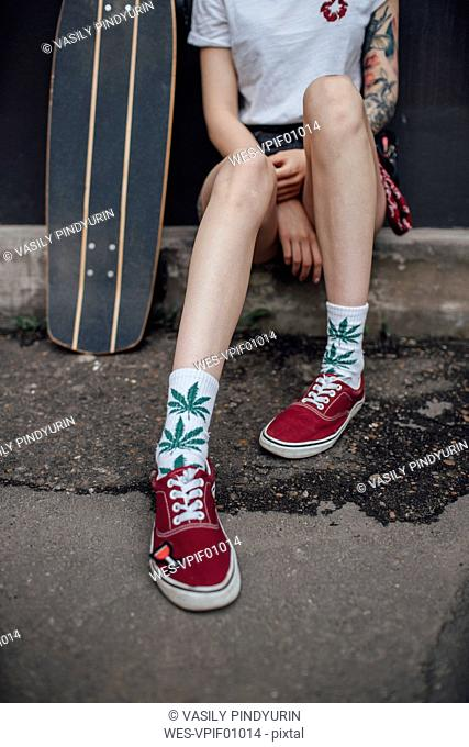 Woman's legs in socks and sneakers sitting next to carver skateboard