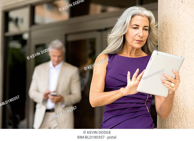 Older Caucasian people using technology outdoors