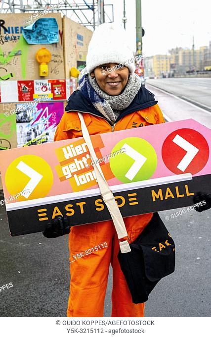 Berlin, Germany. Young Girl attracting attention to East Side Mall shopping center, by standing outside in cold and rainy weather holding a sign, directing