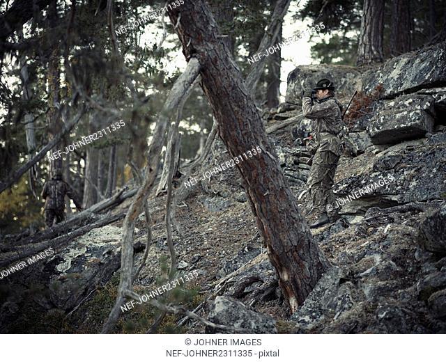 Hunter using binoculars in forest