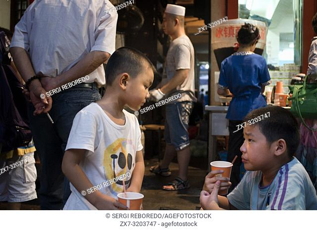 Muslim quarter of Xian, Shaanxi, China, Asia. Silk road, Huimin Street, Beiyuanmen Moslem market. Children at Stall food