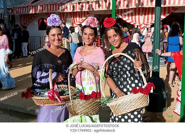 April Fair, Girls wearing a traditional gypsy dress with basket of flowers, Seville, Spain