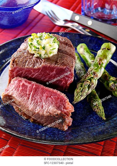 A plate of filet mignon and grilled asparagus