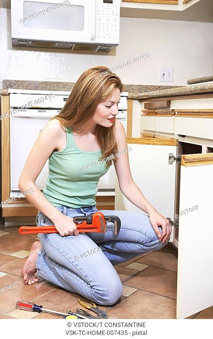 Female plumber fixing kitchen sink