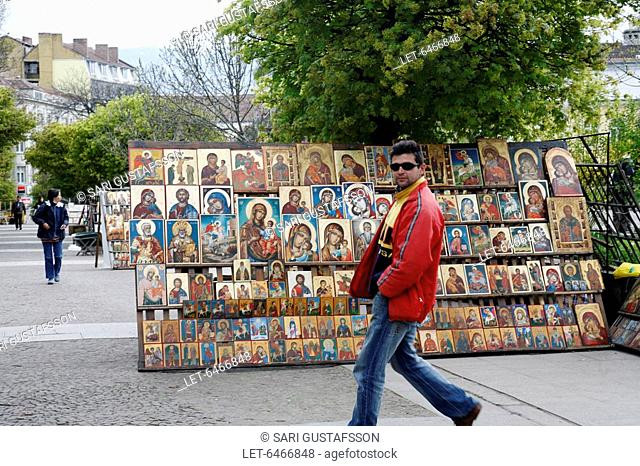 A man passes a souvenir stall with icons in front of St. Alexander Nevsky Cathedral in Sofia, the capital of Bulgaria