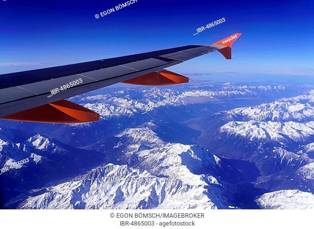 Wing of an Airbus A319 of the airline easyJet over snow-covered Alps, Austria