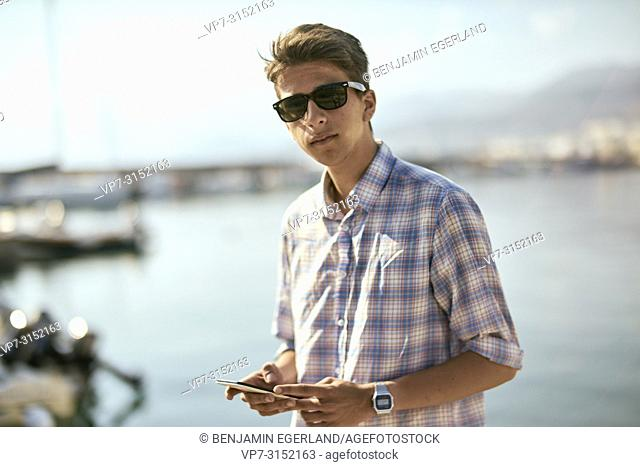young man using smartphone at harbour, seaside, smartwatch, Chersonissos, Crete, Greece
