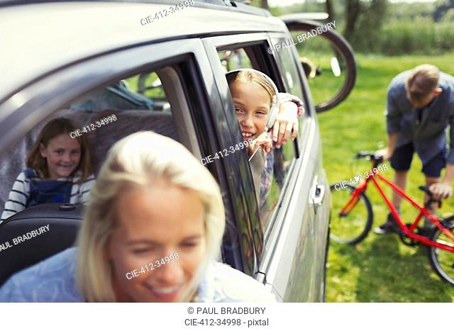 Portrait smiling girl with family inside car