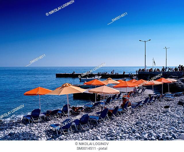 Horizontal vivid stony beach with umbrellas background