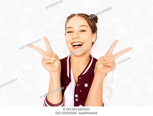 winter, christmas, people, gesture and teens concept - happy smiling pretty teenage girl showing peace sign over gray background and snow