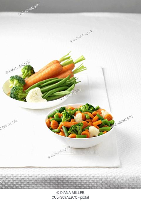 Raw vegetables in bowl with bowl of boiled vegetables