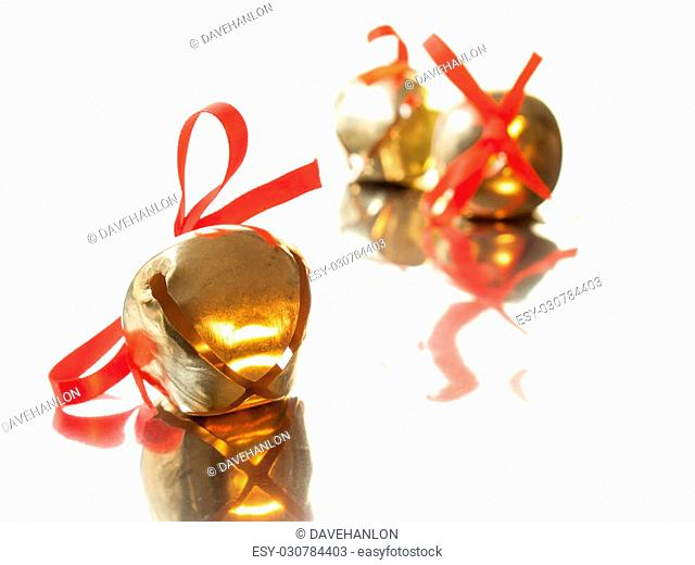shiny golden sleigh bell with red ribbon bow on reflective surface with sleigh bells out of focus in background