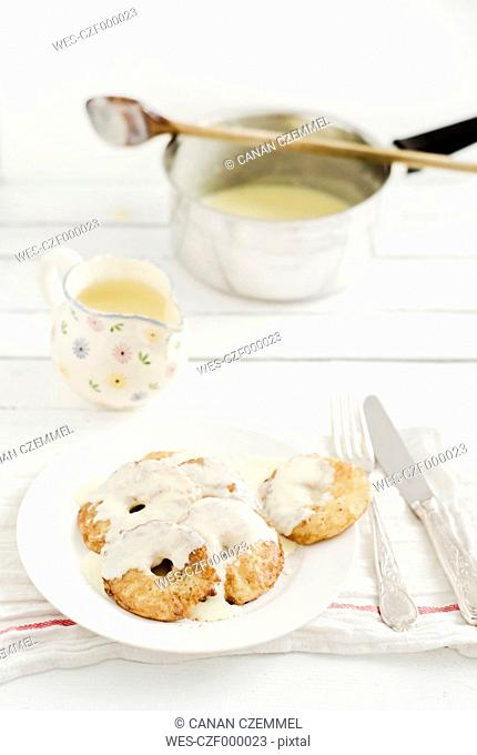 Apple fritters with custard on wooden table, close up