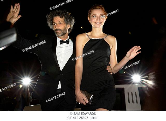 Celebrity couple arriving and waving to paparazzi at event