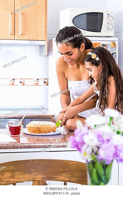 Teenage girl and her little sister in kitchen cutting a cake