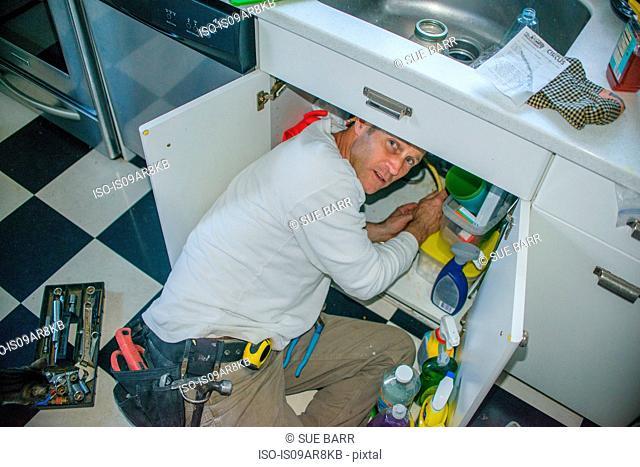 Handyman fixing kitchen sink pipe