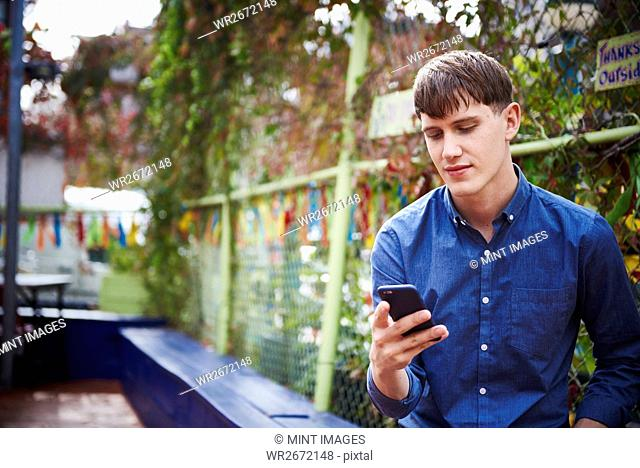 A young man sitting outdoors looking down at a cellphone