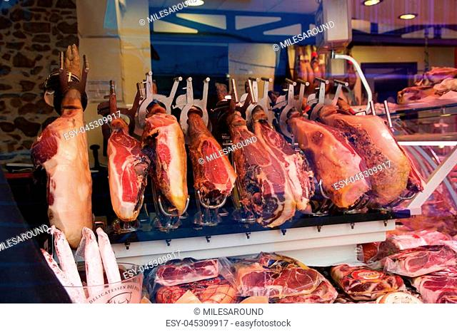 CAMBRILS, SPAIN - AUG 27th, 2017: Spanish ham on a market, jamon iberico in view black leg pork isolated, traditional national spain meat in store