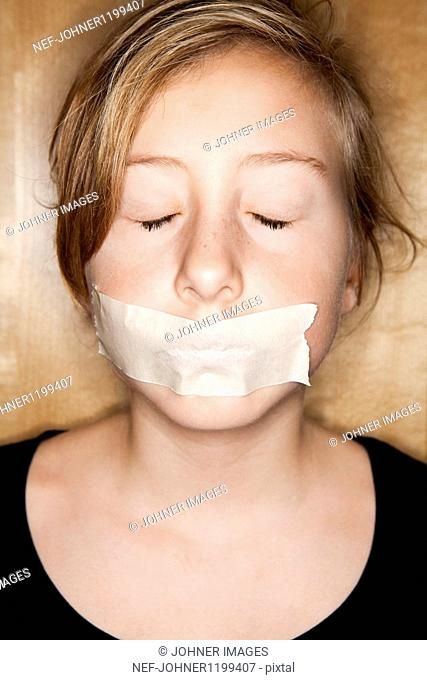 Portrait of young girl with scotch tape over mouth